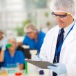 Senior scientist writing medical report — Stock Photo