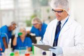 Senior scientist writing medical report — Stock Photo