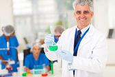 Senior forskare håller laboratorieartiklar av glas — Stockfoto