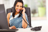 Attractive indian receptionist talking on the phone — Zdjęcie stockowe