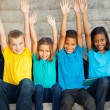 Stock Photo: Happy primary students with hands raised