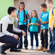 Elementary pupils outside classroom talking to teacher — Stock Photo #28921425