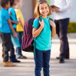 Primary school student carrying backpack — Stock Photo