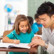 Preschool teacher helping little girl with class work — Stock Photo