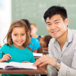 Elementary school teacher helping student in classroom — Stock Photo
