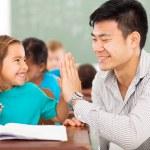 Elementary school teacher and student high five — Stock Photo