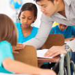 Primary school educator helping a student in class — Stock Photo #28925571