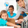 Elementary school teacher helping student — Stock Photo #28925657