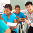 Primary teacher helping student in classroom — Stock Photo