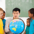 Elementary school students and teacher looking at globe — Stock Photo #28926667