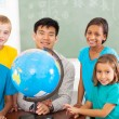Primary school geography teacher and students with a globe — Stock Photo