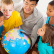 Group of students with teacher looking at the globe — Stock Photo