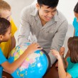 Elementary school teacher teaching geography — Stock Photo #28926845
