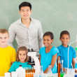 Elementary school students and teacher in chemistry class — Stock Photo