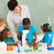 Primary teacher and students in science class — Stock Photo