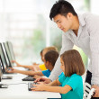 Elementary school teacher teaching in computer room — Stock Photo
