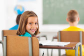 Adorable little schoolgirl in classroom — Stock Photo