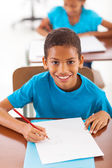 African schoolboy writing classwork — Stock Photo