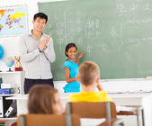 Elementary school teacher applauding — Stock Photo