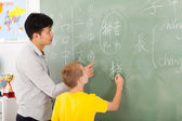 Elementary school teacher helping young boy writing chinese — Stock Photo
