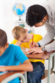 Teacher helping young primary school student — Stock Photo