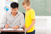 Young male teacher grading school boy's work — Stock Photo