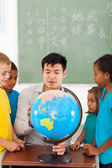 Elementary school students and teacher looking at globe — Stock Photo