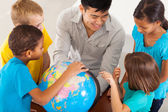 Elementary school teacher teaching geography — Stock Photo