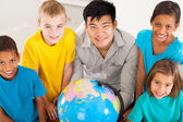 Geography teacher with group of primary students — Stock Photo