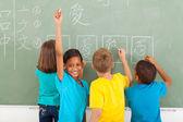 Schoolgirl after writing chinese on blackboard — Stock Photo