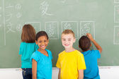 Elementary school students after writing on chalkboard — Stock Photo