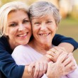Middle aged woman embracing disabled senior mother — Stock Photo #29393863