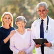 Medical doctor standing with senior patient and her daughter — Stock Photo #29395113