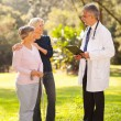 Mid age woman and senior mother talking to doctor — Stock Photo