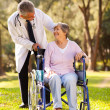 Doctor pushing happy senior patient in wheelchair outdoors — Stock Photo