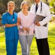 Medical staff and senior patient outdoors — Stok fotoğraf