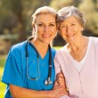 Medical nurse and senior patient outdoors — Foto de Stock