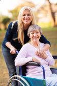 Senior woman in a wheelchair and her daugther — Stock Photo