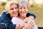Middle aged woman embracing disabled senior mother — Stock Photo