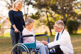 Male doctor talking with handicapped senior woman — Foto Stock