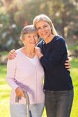 Mature woman with her senior mother outdoors — Stock Photo