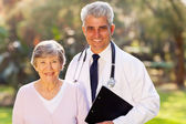 Middle aged doctor and senior patient outdoors — Stock Photo