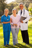 Medical staff and senior patient outdoors — Stock Photo