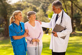 Male doctor talking to recovering senior patient — Stock Photo