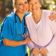 Stock Photo: Caregiver hugging senior patient outdoors