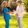 Stock Photo: Female nurse greeting recovering senior patient