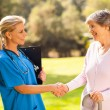 Stock Photo: Mid aged nurse handshaking senior patient
