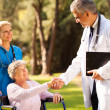 Medical doctor handshaking with senior patient — Stock Photo