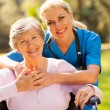 Senior woman in wheelchair outdoors with caring caregiver — Stock Photo #29401607