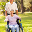 Caring mid age son taking senior mother for a walk — Stock Photo